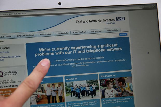 In this posed picture photograph, a woman points to the website of the NHS: East and North Hertfordshire notifying users of a problem in its network, in London on May 12, 2017.  Several British hospitals were hit by cyber attacks on Friday, the country's health service said, forcing some to divert ambulances to other clinics and urge people not to try to contact their doctors. / AFP PHOTO / Daniel LEAL-OLIVAS
